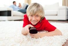 Menino alegre que presta atenção à tevê encontrar-se no assoalho Fotografia de Stock Royalty Free