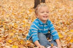 Menino alegre que senta-se na folha amarela. Fotos de Stock