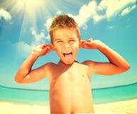 Menino alegre que tem o divertimento na praia Fotografia de Stock Royalty Free