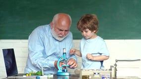 Menino amigável da criança com o professor maduro idoso na sala de aula perto da mesa do quadro-negro Av? e neto Av? e vídeos de arquivo