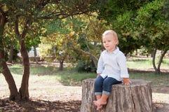 Menino 1 ano de assento velho em um coto de árvore em um dia de verão ensolarado K Imagem de Stock