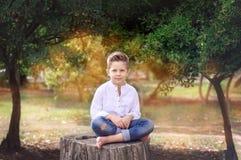 Menino 8 anos de assento velho em um coto de árvore em um dia de verão ensolarado K Fotografia de Stock Royalty Free