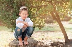 Menino 8 anos de assento velho em um coto de árvore em um dia de verão ensolarado K Foto de Stock