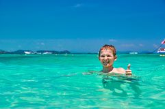 Menino 10 anos de banho velho na criança tropical do mar da água de turquesa que sorri ao mostrar o polegar acima Seascape com cé Fotos de Stock Royalty Free