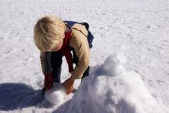 Menino 3 anos de jogo velho com neve no inverno Imagem de Stock
