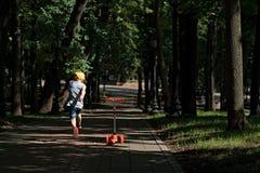 Menino 5 anos velho, com um 'trotinette' na estrada no parque Feriado da família Imagem de Stock