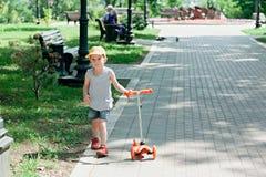 Menino 5 anos velho, com um 'trotinette' na estrada no parque Feriado da família Fotografia de Stock