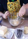 Menino, 12 anos velho, fazendo pedaços de chocolate cookies Imagens de Stock Royalty Free