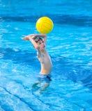 Menino aproximadamente para bater uma esfera na piscina Foto de Stock