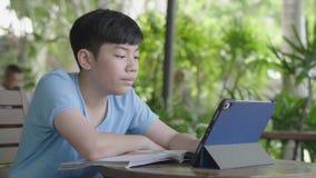 Menino asiático bonito que usa o tablet pc, adolescente novo que faz trabalhos de casa na tabuleta digital com silenciosamente a  filme