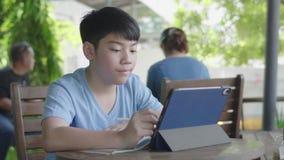 Menino asiático bonito que usa o tablet pc, adolescente novo que faz trabalhos de casa na tabuleta digital com silenciosamente a  vídeos de arquivo