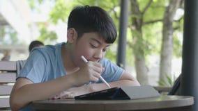 Menino asiático bonito que usa o tablet pc, adolescente novo que faz trabalhos de casa na tabuleta digital com silenciosamente a  video estoque