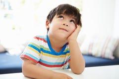 Menino asiático com cabeça no pensamento das mãos Foto de Stock Royalty Free