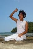Menino asiático com os auriculares na praia. imagem de stock royalty free