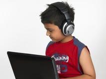 Menino asiático com portátil Fotografia de Stock Royalty Free
