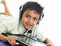 Menino asiático com portátil e auscultadores Imagens de Stock Royalty Free
