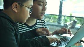 Menino asiático feliz lento do movimento 4K que joga o jogo em linha no laptop junto Menino e amigo confer com a estratégia que t video estoque