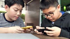 Menino asiático feliz lento do movimento 4K que joga o jogo móvel em linha no telefone esperto junto Menino e amigo confer com a  filme
