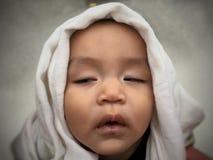 Menino asiático infantil bonito que dorme com o tecido em seu saco foto de stock
