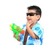 Menino asiático novo com a arma de água no fundo branco Giro de Whoooo! Fotografia de Stock Royalty Free
