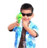 Menino asiático novo com a arma de água no fundo branco Giro de Whoooo! Imagem de Stock