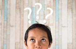 Menino asiático novo que olha ao ponto de interrogação imagem de stock royalty free