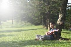 Menino asiático novo que tem o tempo do divertimento que joga o ukelele no parque na manhã ensolarada imagens de stock royalty free