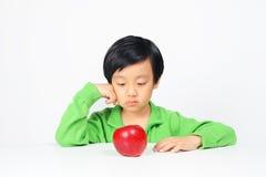Menino asiático novo relutante comer o alimento saudável Fotos de Stock