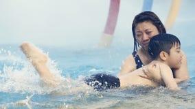 Menino asiático pequeno que aprende como a nadar com sua mãe filme
