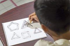 Menino asiático que aprende e que pratica tirar em casa as formas 3D no caderno do desenho na mesa marrom Fotos de Stock Royalty Free