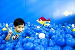 Menino asiático que aumenta dois dedos na sala de jogos completamente das bolas Imagem de Stock