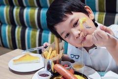 Menino asiático que come batatas fritas felizmente fotos de stock royalty free