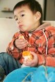 Menino asiático que come a laranja no sofá fotos de stock royalty free