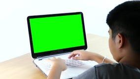 Menino asiático que datilografa em um laptop filme