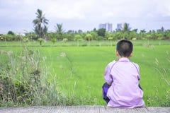 Menino asiático que guarda um telefone e que senta no fundo da rua os campos verdes do arroz fotos de stock royalty free