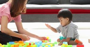 Menino asiático que joga blocos do tijolo com sua mãe video estoque