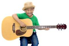 Menino asiático que joga a guitarra no fundo branco isolado foto de stock