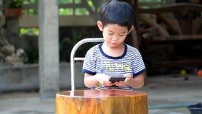 Menino asiático que joga jogos no telefone esperto alegremente, celebração asiática do menino no jogo de vencimento no smartphone video estoque