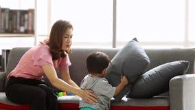 Menino asiático que joga no sofá e que joga blocos do tijolo com sua mãe vídeos de arquivo