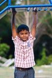 Menino asiático que joga o balanço no campo de jogos Imagem de Stock