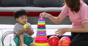 Menino asiático que joga o brinquedo e as bolas com sua mãe vídeos de arquivo
