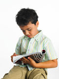 Menino asiático que lê um compartimento Fotografia de Stock