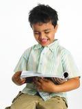 Menino asiático que lê um compartimento Fotografia de Stock Royalty Free
