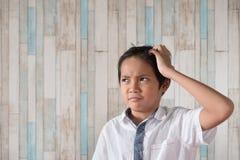 Menino asiático que risca sua cabeça expressão confusa do menino foto de stock