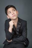 Menino asiático pequeno na virada preta do terno, cara da depressão Fotografia de Stock Royalty Free