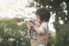 Menino asiático que beija o gatinho americano do cabelo curto Imagens de Stock