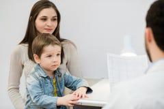 Menino assustado com sua mãe que senta-se no doutor do pediatra, psicólogo Imagens de Stock Royalty Free