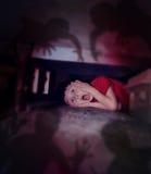 Menino assustado que olha sombras da noite sob a cama Imagem de Stock Royalty Free