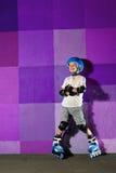 Menino atlético pequeno bonito no rolo que está contra a parede roxa dos grafittis imagens de stock