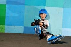 Menino atlético pequeno bonito no rolo que senta-se contra a parede azul dos grafittis fotografia de stock royalty free